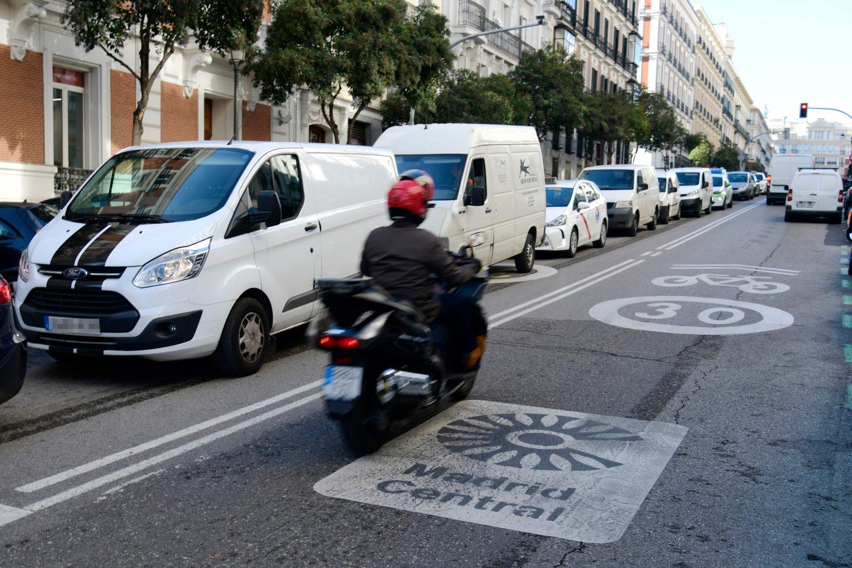 """Una moto circula por una calle de Madrid sobre las señales de """"Madrid Central"""""""